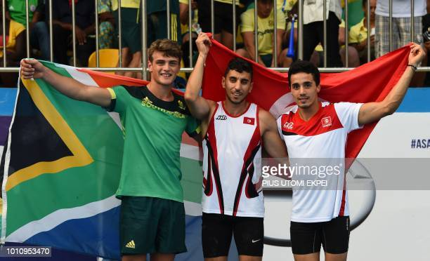 Gold medalist Tunisian Mohamed Romdhana flanked by silver medalist South African Valco Van Wyk and bronze medalist Tunisian Mejdi Chehata hold their...