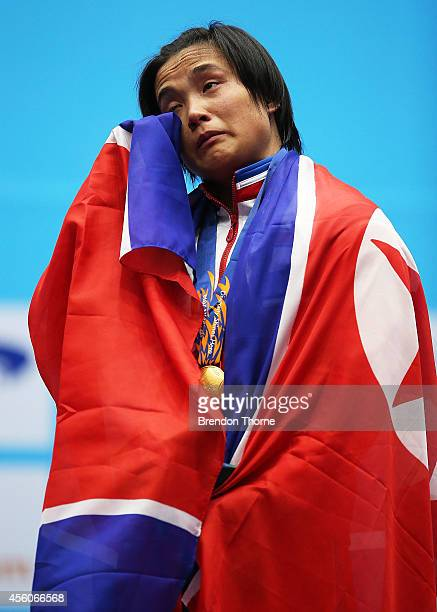 Gold medalist, Unju Kim of North Korea shows her emotions during her nations national anthem after breaking the new world record in clean and jerk...