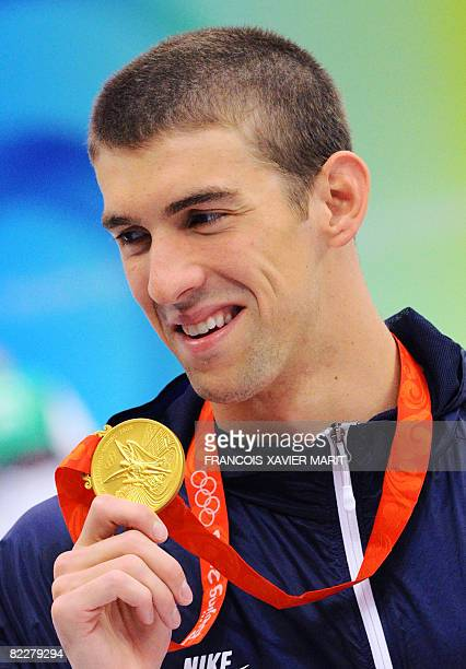 Gold medalist US swimmer Michael Phelps holds his medal after the men's 200m butterfly swimming medal ceremony at the National Aquatics Center during...