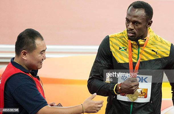 Gold medalist Usain Bolt of Jamaica is presented with a gift by Tao Song of CCTV the segway driver who accidentally collided with him following the...