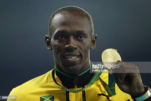 Gold medalist Usain Bolt of Jamaica poses on the podium during the medal ceremony for the Men's 100 metres on Day 10 of the Rio 2016 Olympic Games at...