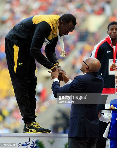 Gold medalist Usain Bolt of Jamaica receives his medal from Frank Fredericks on the podium during the medal ceremony for the Men's 200 metres during...