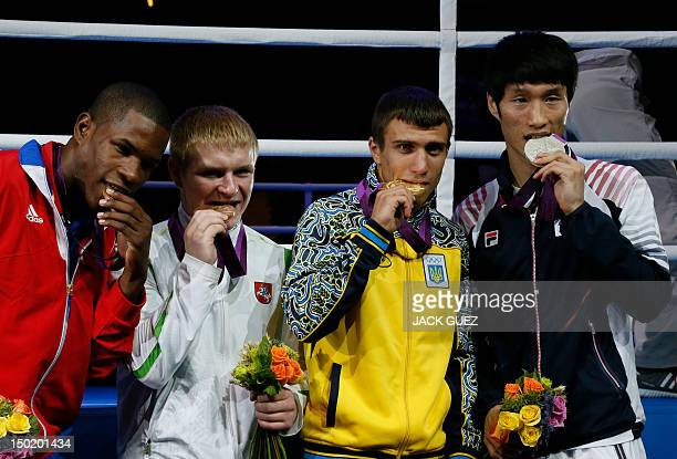 Gold medalist Vasyl Lomachenko of the Ukraine stands on the podium with silver medalist Soonchul Han of South Korea bronze medalists Yasniel Toledo...