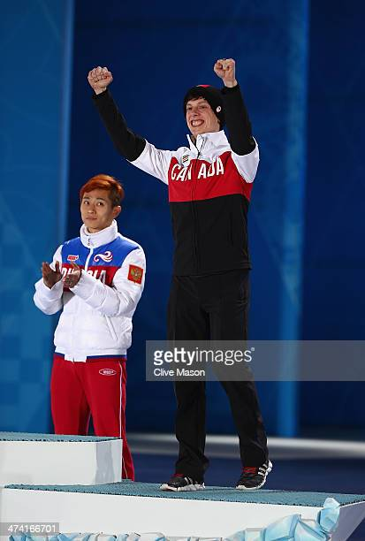 Gold medalist Victor An of Russia and bronze medalist Charle Cournoyer of Canada celebrate during the medal ceremony for the Short Track Men's 500m...