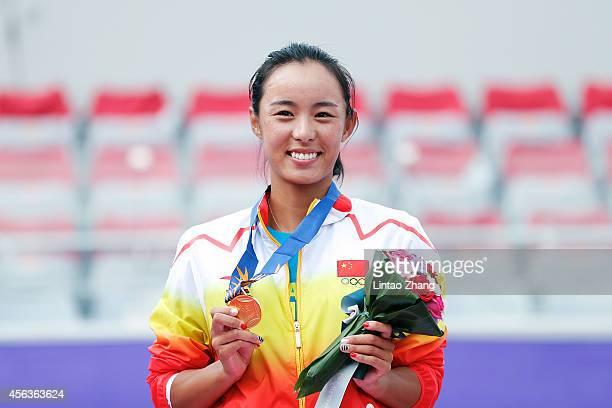 Gold medalist Wang Qiang of China celebrates during the medal ceremony after the Tennis Women's Singles Gold Medal Match on day eleven of the 2014...