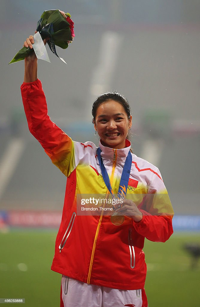 Gold medalist Wei Yongli of China celebrates on the podium during the victory ceremony for the Women's 100m during day nine of the 2014 Asian Games at Incheon Asiad Main Stadium on September 28, 2014 in Incheon, South Korea.
