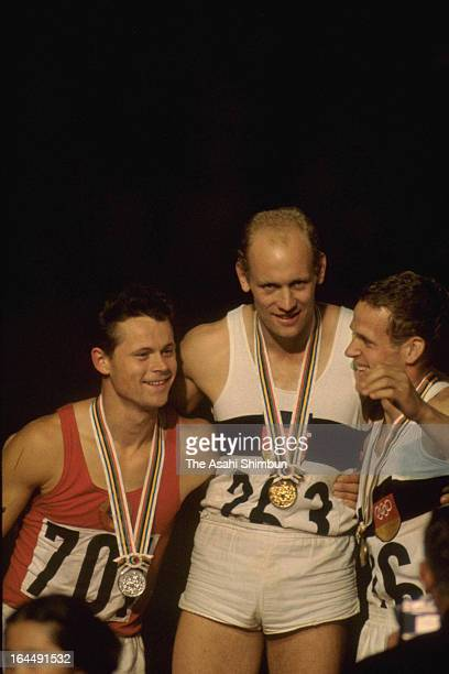 Gold Medalist Willi Holdorf of Germany Silver Medalist Rein Aun of Soviet Union and Bronze Medalist Hans Walde of Germany hug each other after the...