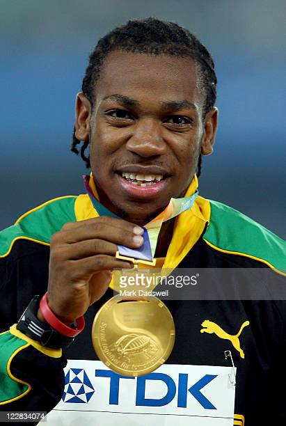 Gold medalist Yohan Blake of Jamaica celebrates on the podium with his medal for the men's 100 metres during day three of 13th IAAF World Athletics...