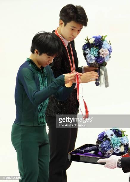 Gold medalist Yuma Kagiyama of Japan picks up his medal while bronze medalist Lucas Tsuyoshi Honda of Japan watches on the podium at the medal...