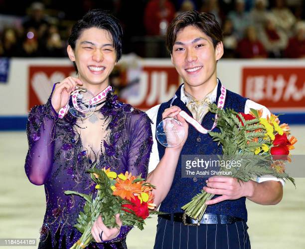 Gold medalist Yuzuru Hanyu and bronze medalist Keiji Tanaka of Japan pose for photographs at the medal ceremony in the Men's Singles during the ISU...