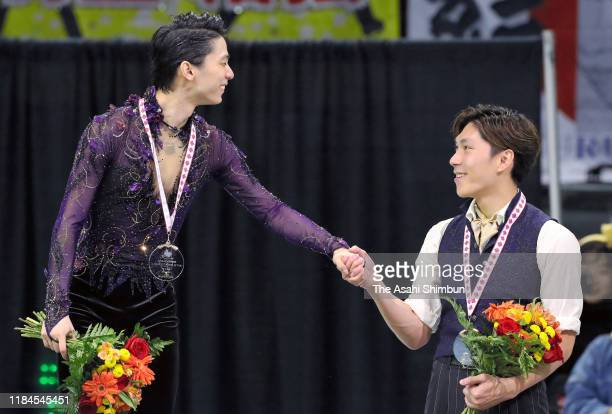 Gold medalist Yuzuru Hanyu and bronze medalist Keiji Tanaka of Japan shake hands on the podium at the medal ceremony in the Men's Singles during the...