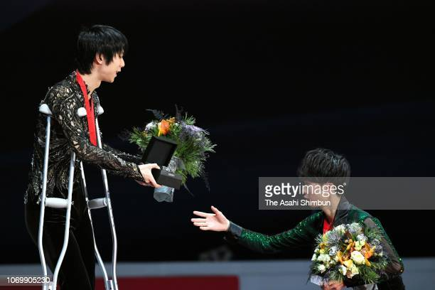 Gold medalist Yuzuru Hanyu of Japan and bronze medalist Kazuki Tomono of Japan shake hands at the medal ceremony for the Men's Singles on day three...