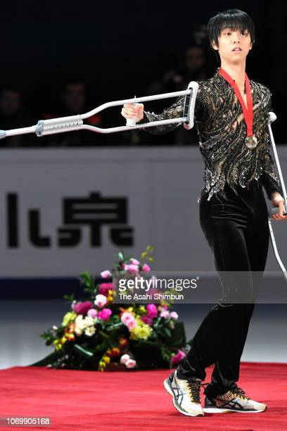 Gold medalist Yuzuru Hanyu of Japan walks with crutches at the medal ceremony for the Men's Singles on day three of the ISU Grand Prix of Figure...