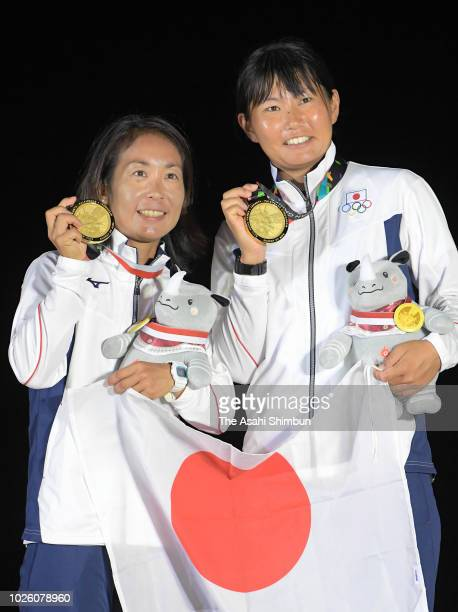 Gold medalists Ai Yoshida and Miho Yoshioka of Japan celebrate on the podium at the medal ceremony for the Sailing Women's 470 on August 31 2018 in...