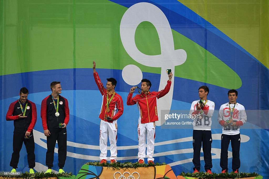 Gold medalists Aisen Chen and Yue Lin of China celebrate on the podium during the medal ceremony for the Men's Diving Synchronised 10m Platform Final on Day 3 of the Rio 2016 Olympic Games at Maria Lenk Aquatics Centre on August 8, 2016 in Rio de Janeiro, Brazil.