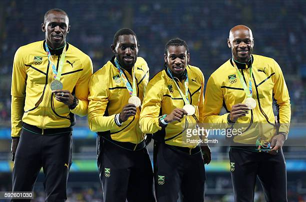 Gold medalists Asafa Powell, Yohan Blake, Nickel Ashmeade and Usain Bolt of Jamaica stand on the podium during the medal ceremony for the Men's 4 x...