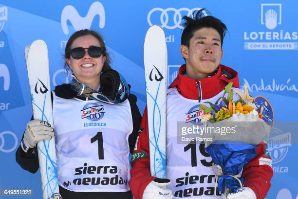 Gold medalists Britteny Cox of Australia and Ikuma Horishima of Japan pose during the flower ceremony for the Men's and Women's Moguls on day one of...