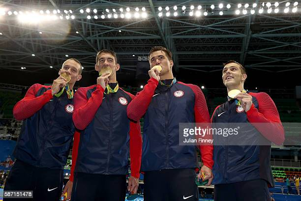 Gold medalists Caeleb Dressell Michael Phelps Nathan Adrian and Ryan Held of the United States kiss their gold medals during the medal ceremony for...