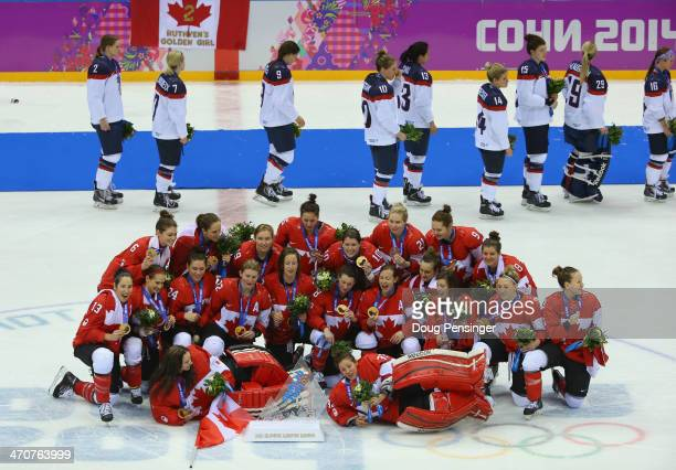 Gold medalists Canada celebrate during the flower ceremony as silver medalists the United States leave the ice for the Ice Hockey Women's Gold Medal...