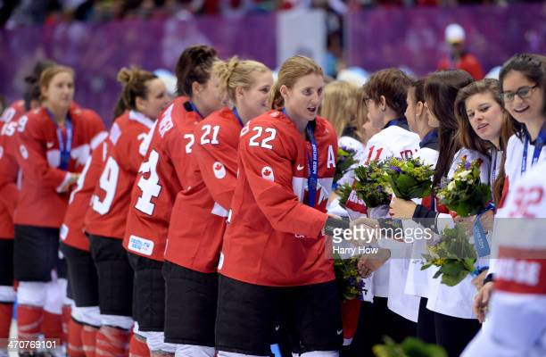 Gold medalists Canada greet bronze medalists Switzerland during the flower ceremony for the Ice Hockey Women's Gold Medal Game on day 13 of the Sochi...