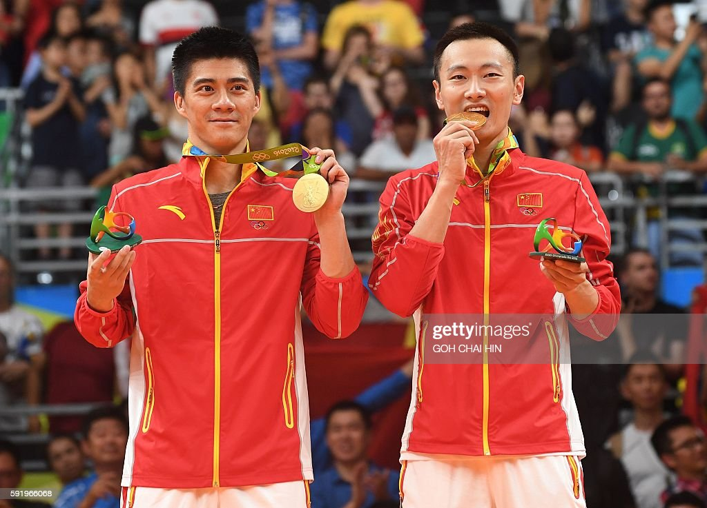 Gold medalists China's Zhang Nan and China's Fu Haifeng (L) stand with their medals on the podium following the men's doubles Gold Medal badminton match at the Riocentro stadium in Rio de Janeiro on August 19, 2016, for the Rio 2016 Olympic Games. / AFP / GOH Chai Hin