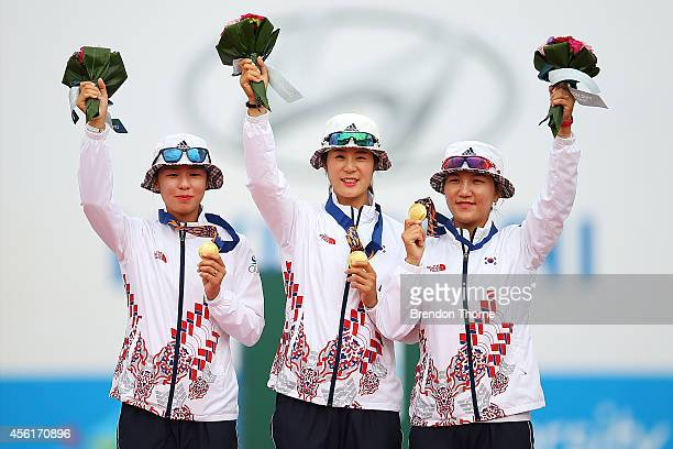 Gold medalists, Choi Bomin, Kim Yunhee and Seok Jihyun of South Korea pose atop the podium following the Compound Women's Team Gold Medal Match...