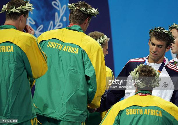 Gold medalists Darian Townsend Lyndon Ferns Mark Roland Schoeman and Ryk Neethling of South Africa greets Michael Phelps of USA during the men's...