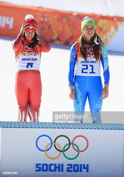 Gold medalists Dominique Gisin of Switzerland and Tina Maze of Slovenia look on during the flower ceremony for during the Alpine Skiing Women's...