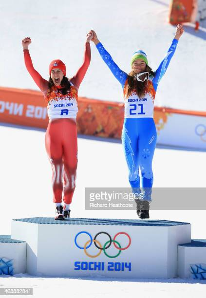 Gold medalists Dominique Gisin of Switzerland and Tina Maze of Slovenia celebrate on the podium during the flower ceremony for during the Alpine...