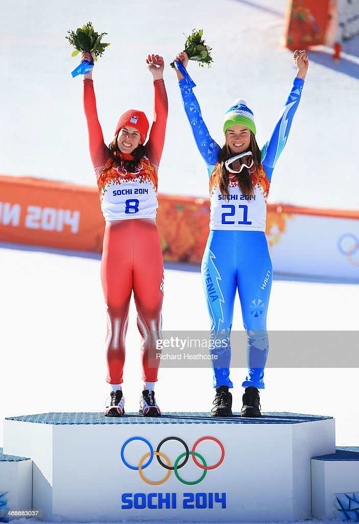 Gold medalists Dominique Gisin of Switzerland (L) and Tina Maze of Slovenia celebrate on the podium during the flower ceremony for during the Alpine Skiing Women's Downhill on day 5 of the Sochi 2014 Winter Olympics at Rosa Khutor Alpine Center on February 12, 2014 in Sochi, Russia.