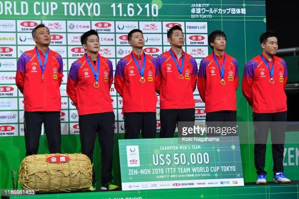 Gold medalists Fan Zhendong, Ma Long, head coach Qin Zhijian, Xu Xin, Lin Gaoyuan and Liang Jingkun of China pose for photographs during the medal...