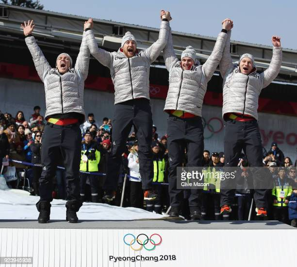 gold medalists Francesco Friedrich Candy Bauer Martin Grothkopp and Thorsten Margis of Germany celebrate on the podium during the medal ceremony...