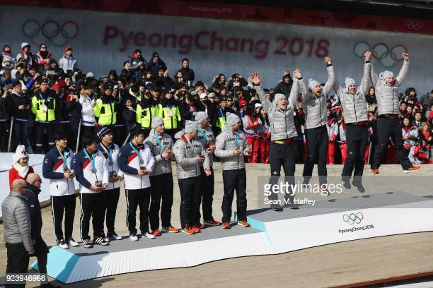 Gold medalists Francesco Friedrich Candy Bauer Martin Grothkopp and Thorsten Margis of Germany celebrate on the podium alongside joint silver...