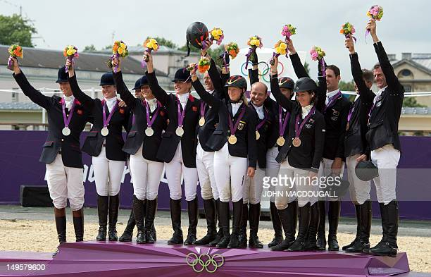 Gold medalists Germany's Peter Thomsen Dirk Schrade Sandra Auffarth Michael Jung and Ingrid Klimke pose on the podium with Silver medalists Britain's...