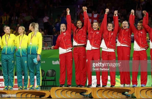 Gold medalists Helen Housby and England celebrate as Australia captain Caitlin Bassett looks away during the medal ceremony for the Netball Gold...