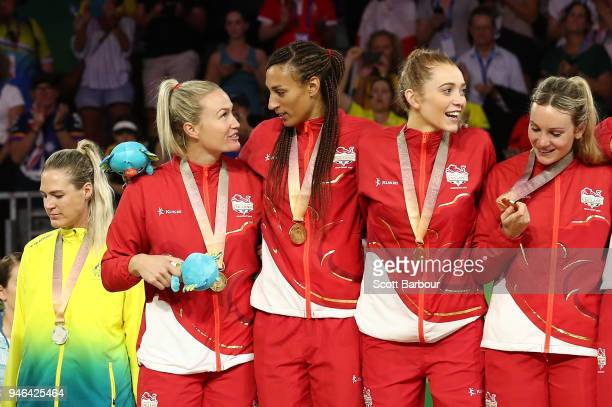 Gold medalists Helen Housby Geva Mentor and England celebrate as Australia captain Caitlin Bassett looks away during the medal ceremony for the...