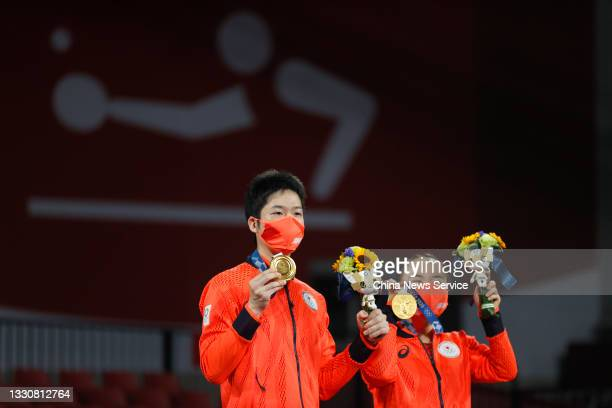 Gold medalists Jun Mizutani and Mima Ito of Japan celebrate on the podum after winning the Mixed Doubles Gold Medal Match against Xu Xin and Liu...
