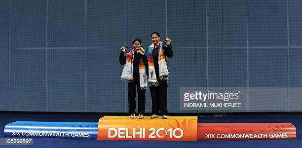 Gold medalists Jwala Gutta and Ashwini Ponnappa Machimanda of India pose on the awards podium after winning against Sari Shinta Mulia and Yao Lei of...
