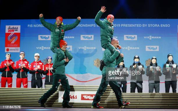 Gold medalists Karl Geiger and Stephan Leyhe carry Markus Eisenbichler and Richard Freitag of Germany on shoulders during the medal ceremony for the...