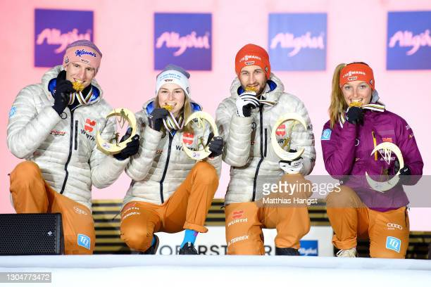 Gold medalists Karl Geiger, Anna Rupprecht, Markus Eisenbichler and Katharina Althaus of Germany celebrate during the medal ceremony for the Ski...