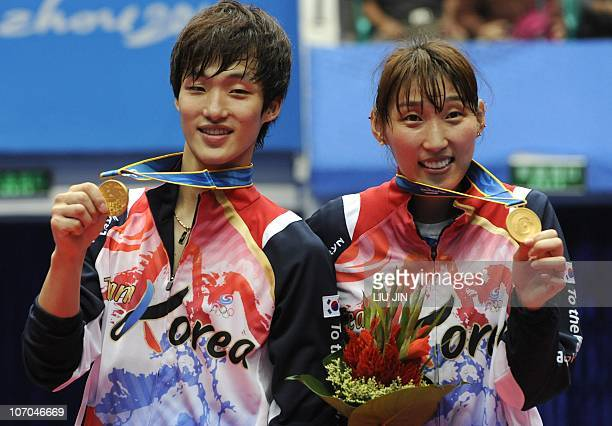 Gold medalists Lee HyoJung and Shin BaekCheol of South Korea pose on the podium during an award ceremony for the mixed doubles final against Zhang...