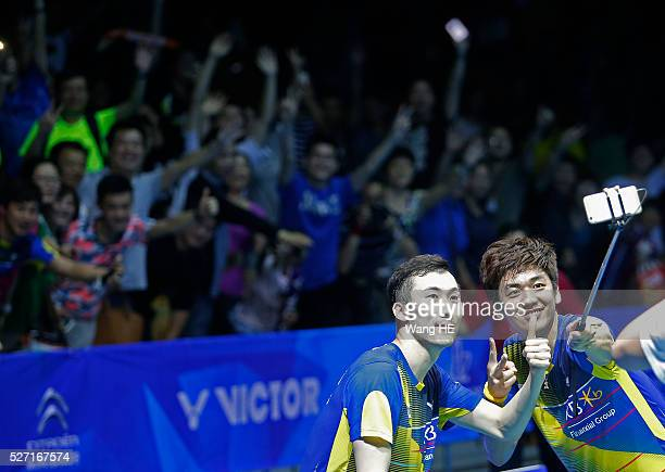 Gold medalists Lee Yong Dae and Yoo Yeon Seong of South Korea use a selfie stick to take photos with fans after winning the men's doubles final match...