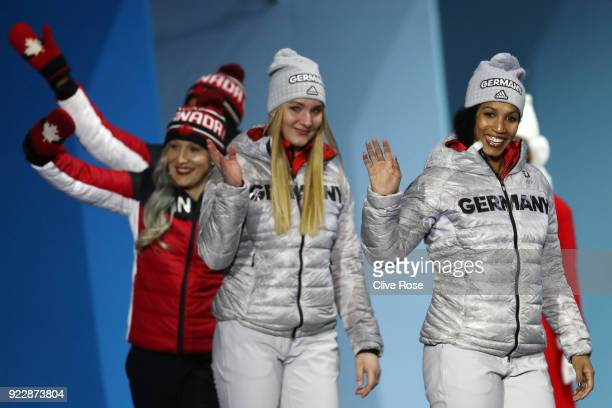 Gold medalists Lisa Buckwitz and Mariama Jamanka of Germany and bronze medalists Phylicia George and Kaillie Humphries of Canada walk on stage for...