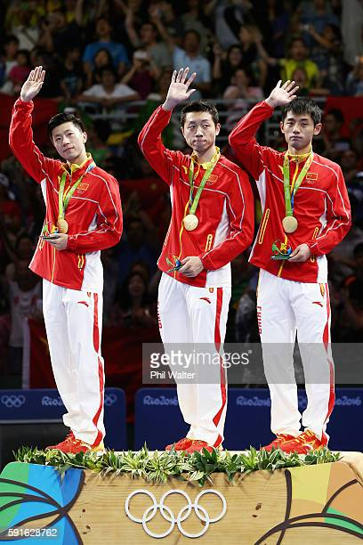 Gold medalists Long Ma, Xin Xu, and Jike Zhang of China celebrate during the medals ceremony after the Men's Table Tennis gold medal match against...
