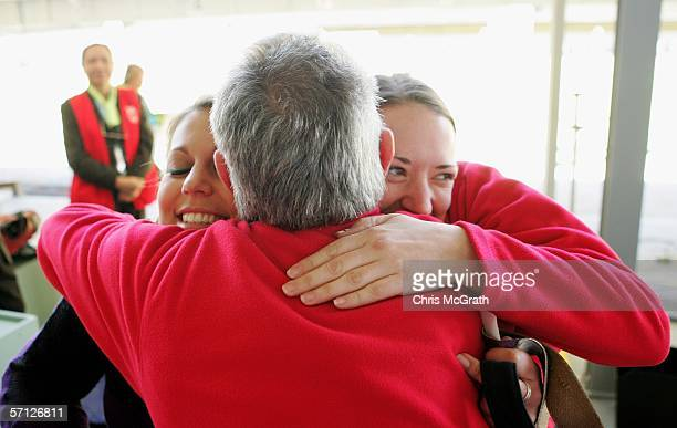 Gold Medalists, Louise Minett and Becky Spicer of England embrace their coach Robin Taylor after winning the Women's 50m Rifle 3 Positions Pairs...