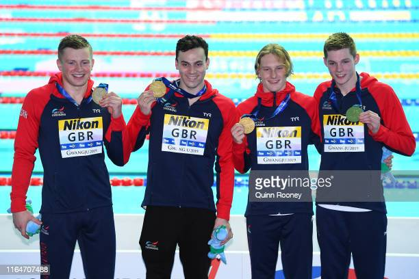 Gold medalists Luke Greenbank Adam Peaty James Guy and Duncan Scott of Great Britain celebrate on the podium at the medal ceremony for the Men's...