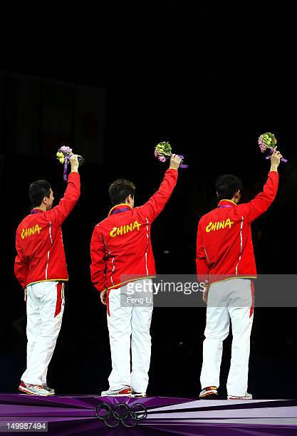 Gold medalists Ma Long , Wang Hao and Zhang Jike of China celebrate on the podium during the medal ceremony for the Men's Team Table Tennis on Day 12...