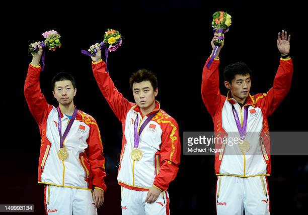 Gold medalists Ma Long, Wang Hao and Zhang Jike of China celebrate on the podium during the medal ceremony for the Men's Team Table Tennis on Day 12...