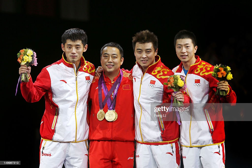 Gold medalists Ma Long (L), Wang Hao (2nd R) and Zhang Jike of China (R) celebrate with their coach Liu Guoliang (2nd L) after putting their medals around his neck during the medal ceremony for the Men's Team Table Tennis on Day 12 of the London 2012 Olympic Games at ExCeL on August 8, 2012 in London, England.