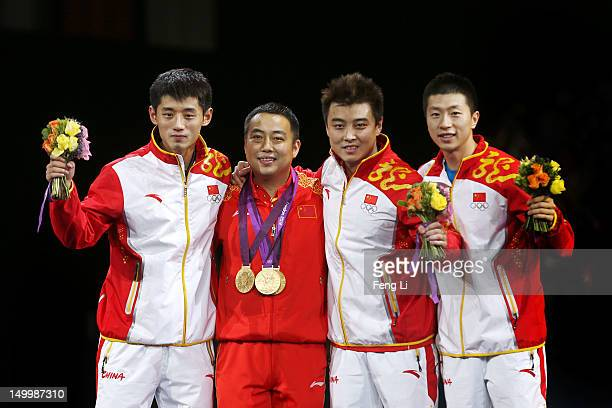 Gold medalists Ma Long , Wang Hao and Zhang Jike of China celebrate with their coach Liu Guoliang after putting their medals around his neck during...